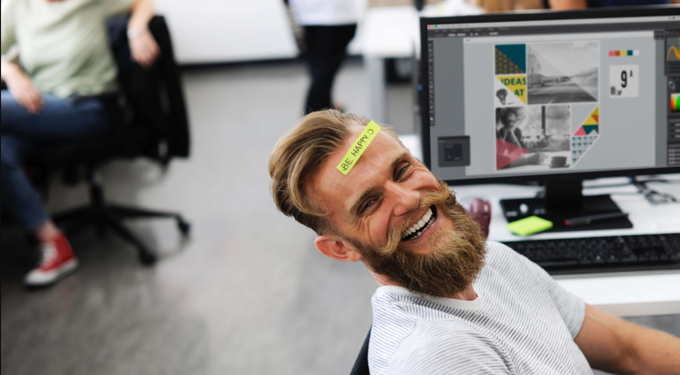 One man at work looking at the camera with a post-it on the forehead saying 'happy'